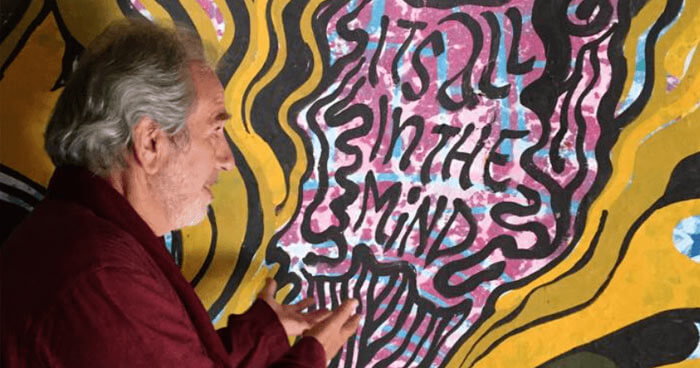 Bruce Lipton looking at Beatles artwork