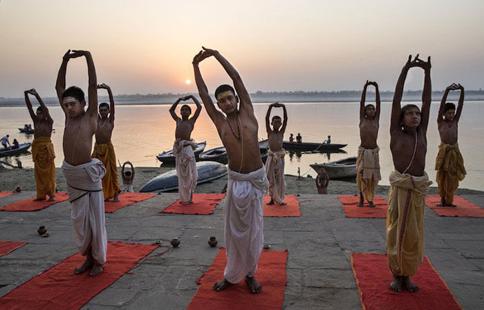 Young Indian Hindu Brahmins training to be priests perform yoga on a ghat on the Ganges