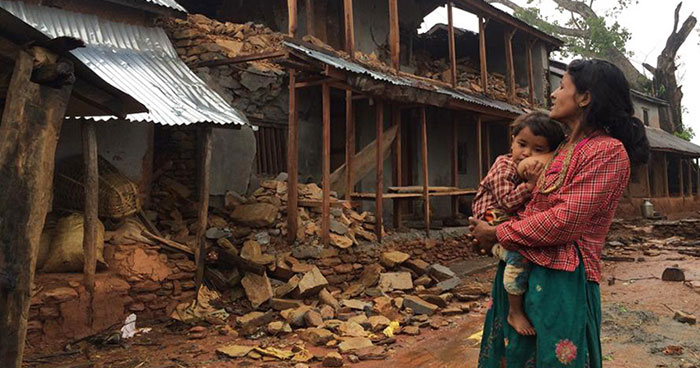 Nepalese mother and child surveying the damage to homes after the Earthquake